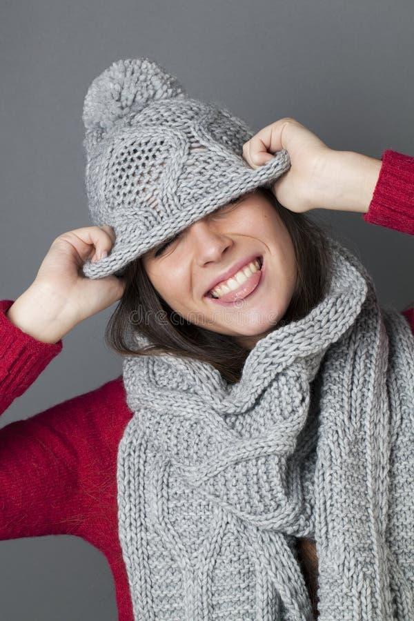 愉快的女性少年耍笑在掩藏在冬天帽子下 免版税库存照片