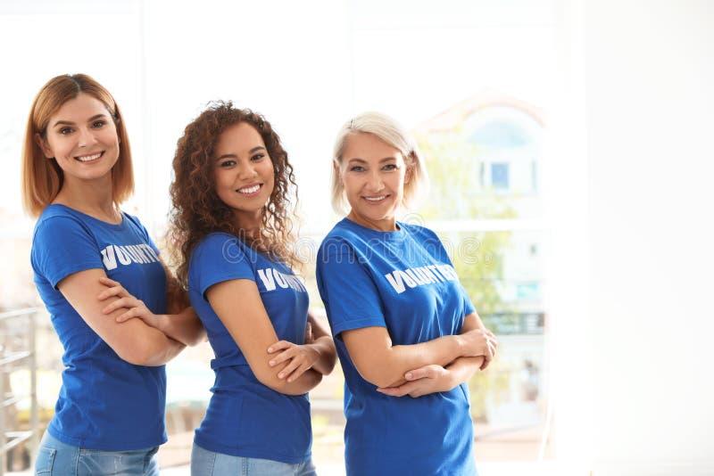 愉快的女性志愿者画象制服的户内 免版税库存照片