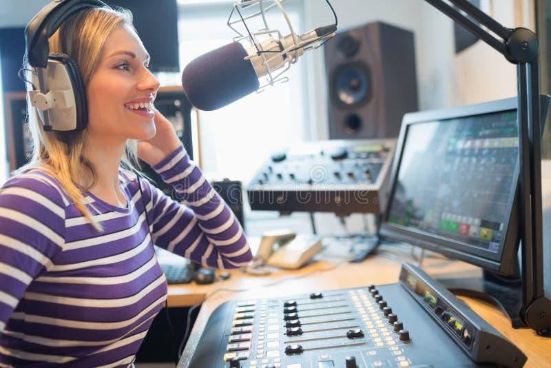 愉快的女性无线电主人广播在演播室 免版税库存照片