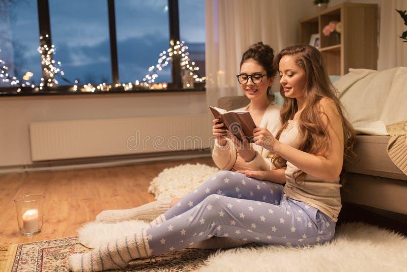 愉快的女性朋友阅读书在家 免版税库存图片