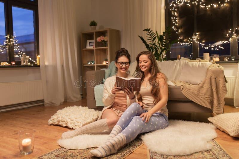 愉快的女性朋友阅读书在家 库存图片