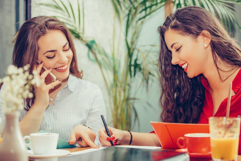 愉快的女性朋友,一起读笔记和指向在哪里的学生签合同 免版税库存图片
