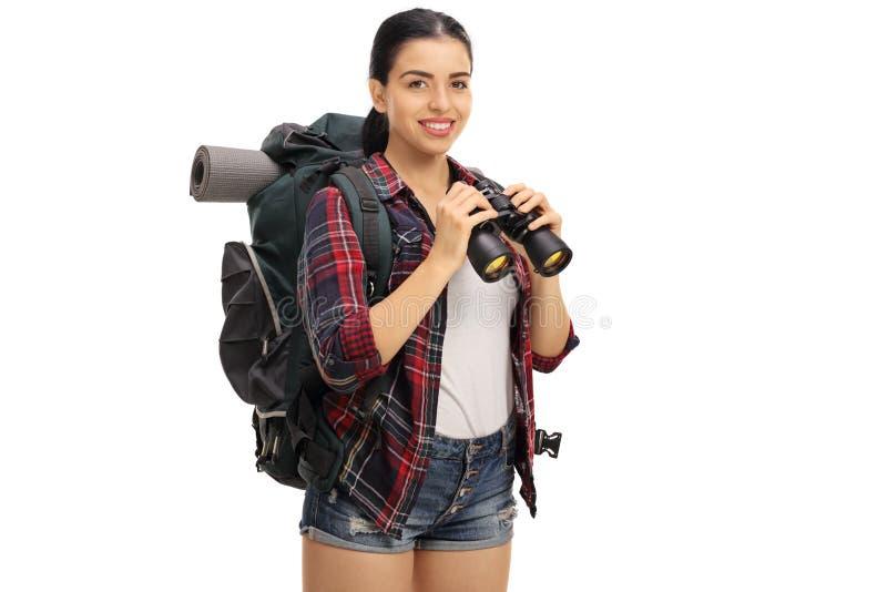 愉快的女性的远足者拿着双筒望远镜 图库摄影