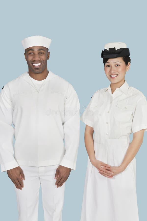 愉快的女性美国海军官员画象有男性水手的在浅兰的背景 免版税库存图片