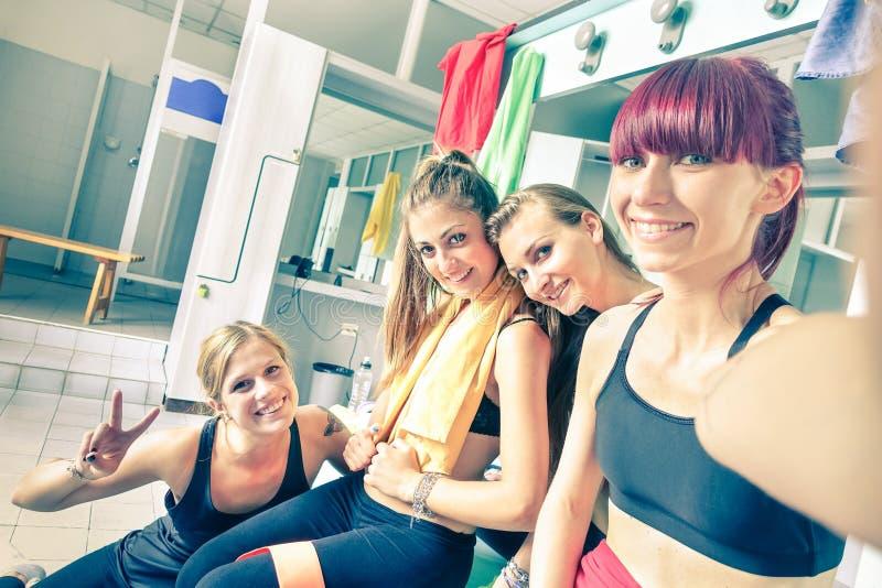 愉快的女朋友在健身房化装室编组采取selfie 免版税库存照片