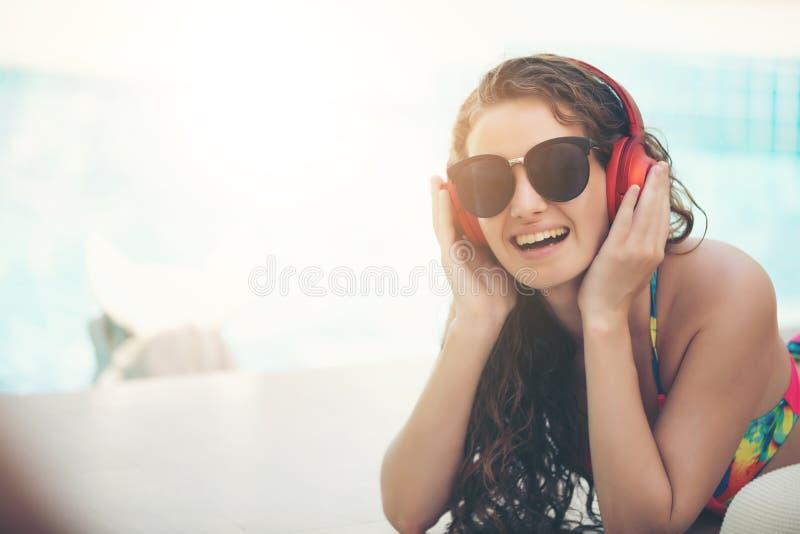 愉快的女服比基尼泳装读书并且听到音乐在s 库存照片