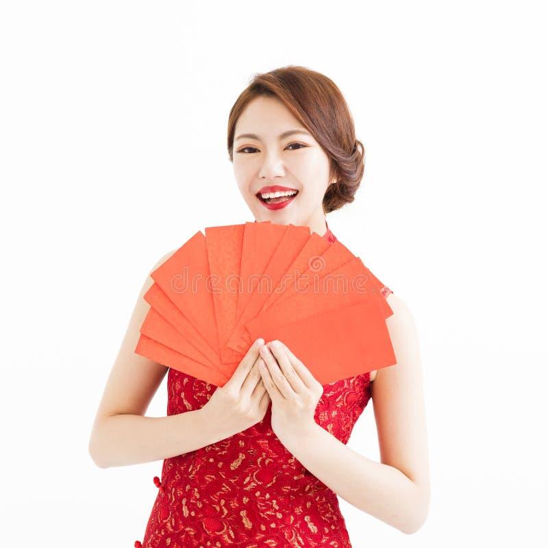 愉快的女服cheongsam和显示红色信封 免版税库存图片