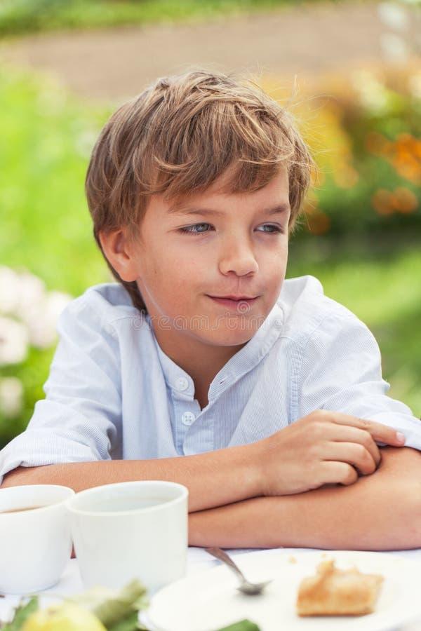 愉快的好男孩饮用的茶在夏天绿色庭院里 库存图片