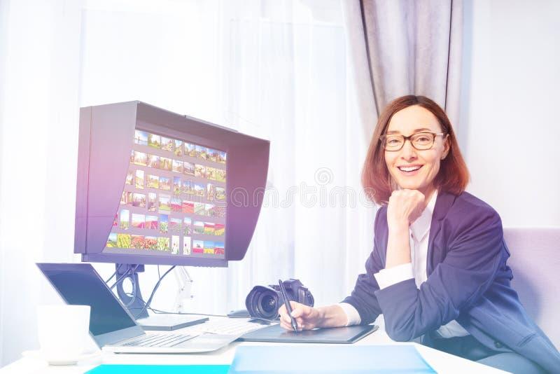 愉快的妇女与图形输入板一起使用在办公室 库存图片