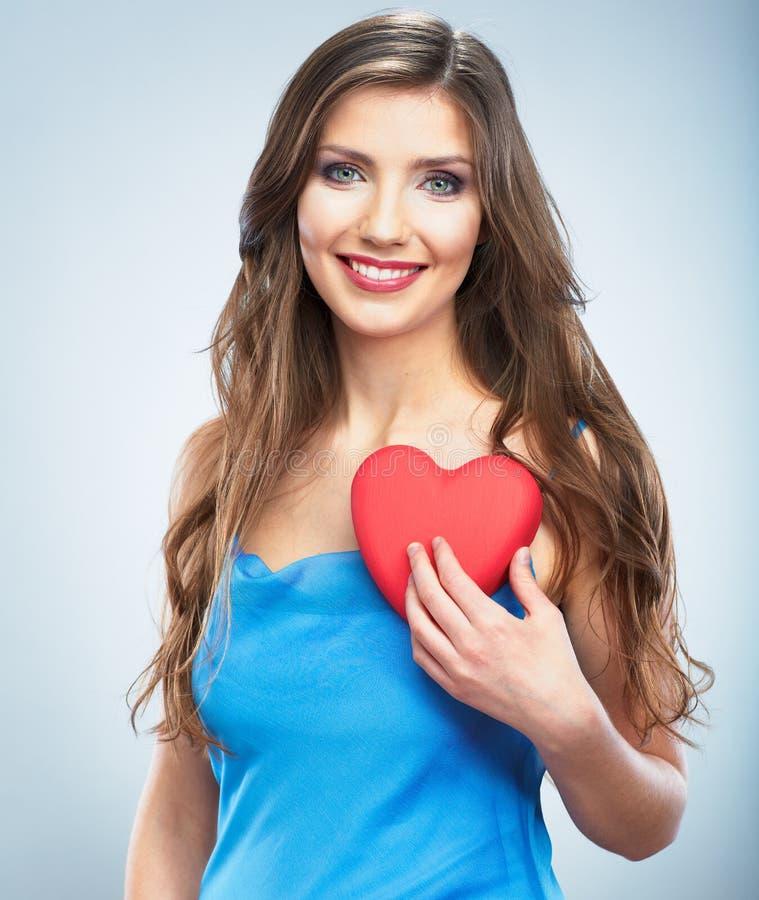 年轻愉快的妇女举行爱标志红色心脏。在studi 库存照片