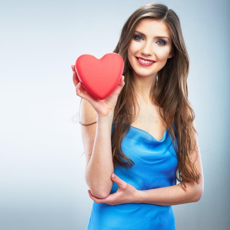 年轻愉快的妇女举行爱标志红色心脏 隔绝在studi 免版税库存照片