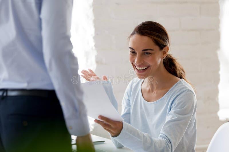 愉快的妇女从上司得到促进通知 免版税库存照片