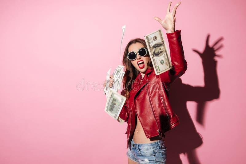 年轻愉快的妇女优胜者投掷的金钱钞票的画象 免版税库存照片