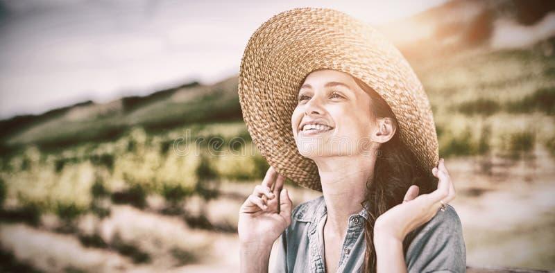 愉快的妇女佩带的太阳帽子,当看时 免版税库存图片