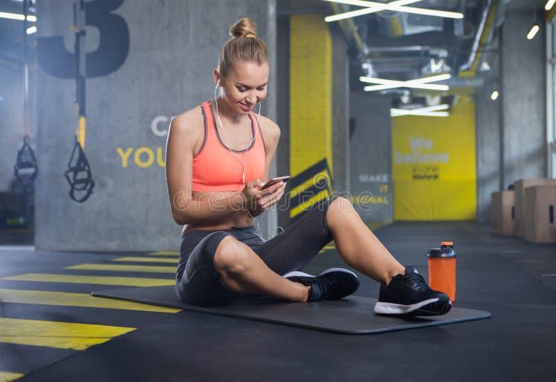 愉快的妇女使用智能手机在训练期间户内 免版税库存照片
