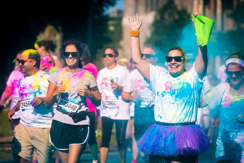 愉快的妇女参加颜色Vibe 5K比赛 库存图片