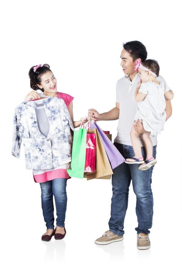 愉快的妇女和她的家庭尝试的衣裳 图库摄影