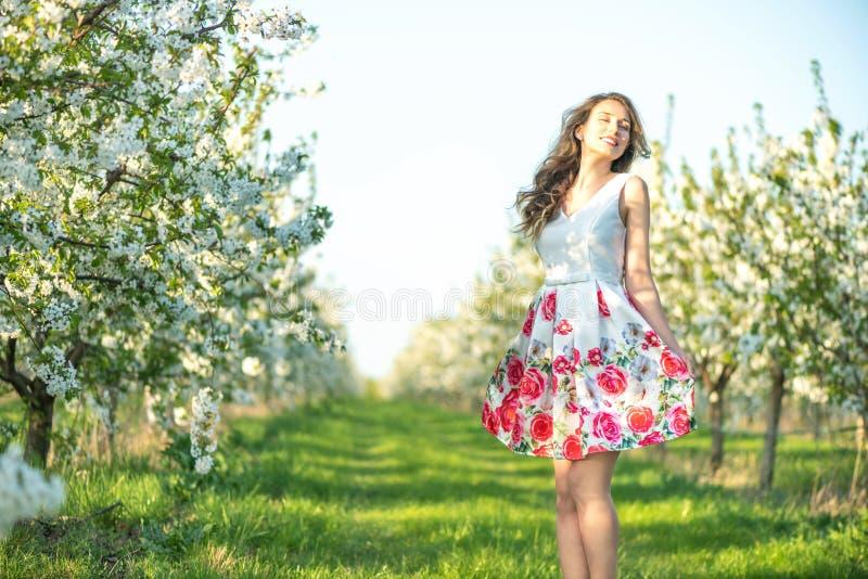 愉快的妇女在一个果树园春天 享受晴朗的温暖的天 减速火箭的样式礼服 开花的开花樱桃树 免版税库存照片