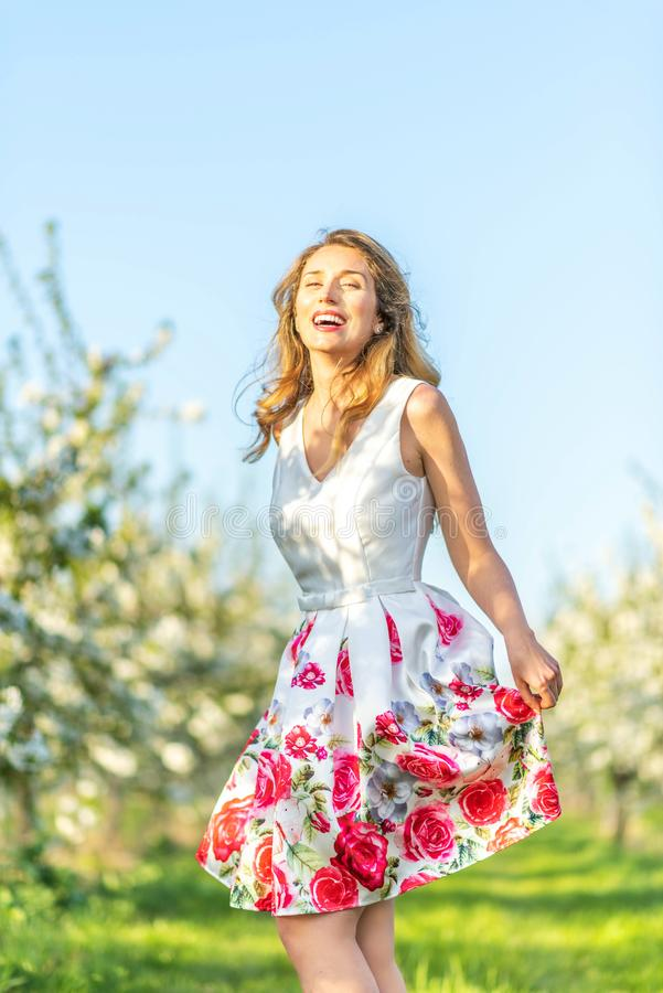 愉快的妇女在一个果树园春天 享受晴朗的温暖的天 减速火箭的样式礼服 开花的开花樱桃树 免版税库存图片