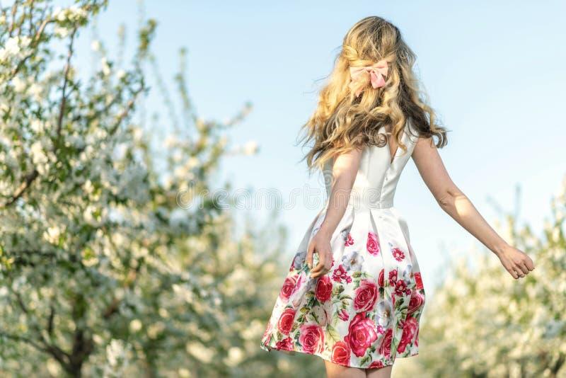 愉快的妇女在一个果树园春天 享受晴朗的温暖的天 减速火箭的样式礼服 开花的开花樱桃树 库存照片