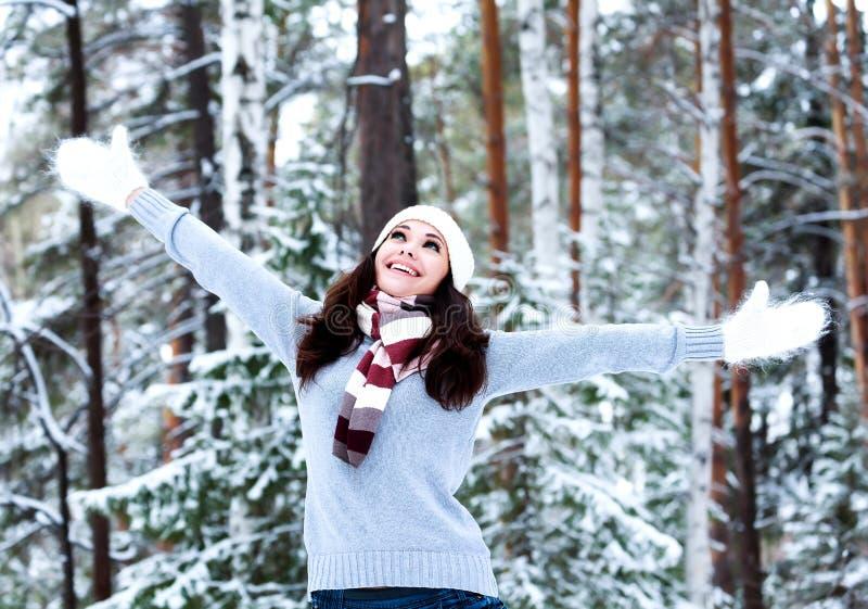 愉快的妇女在冬天森林里 免版税库存照片