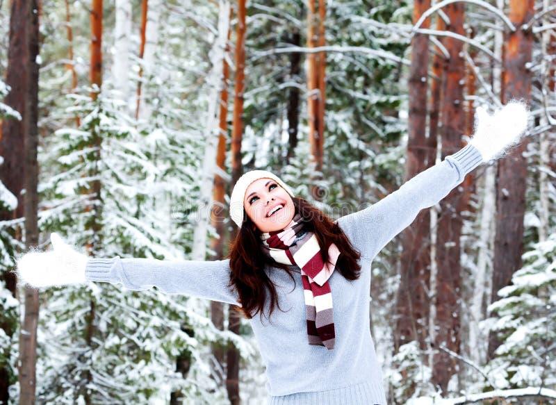 愉快的妇女在冬天森林里 库存照片