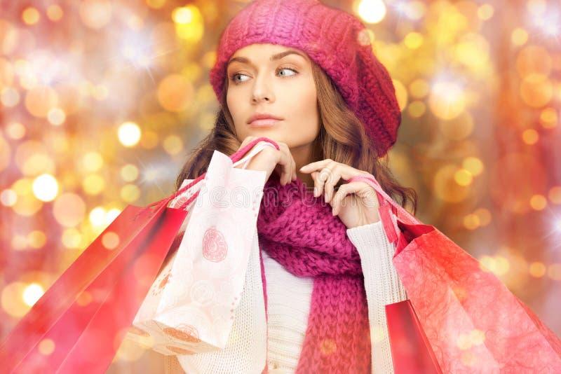 愉快的妇女在冬天穿衣与购物袋 免版税库存图片