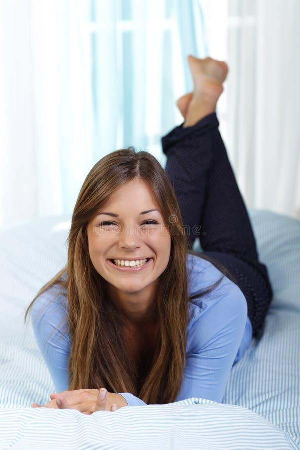 愉快的妇女在她的床放置 免版税库存照片