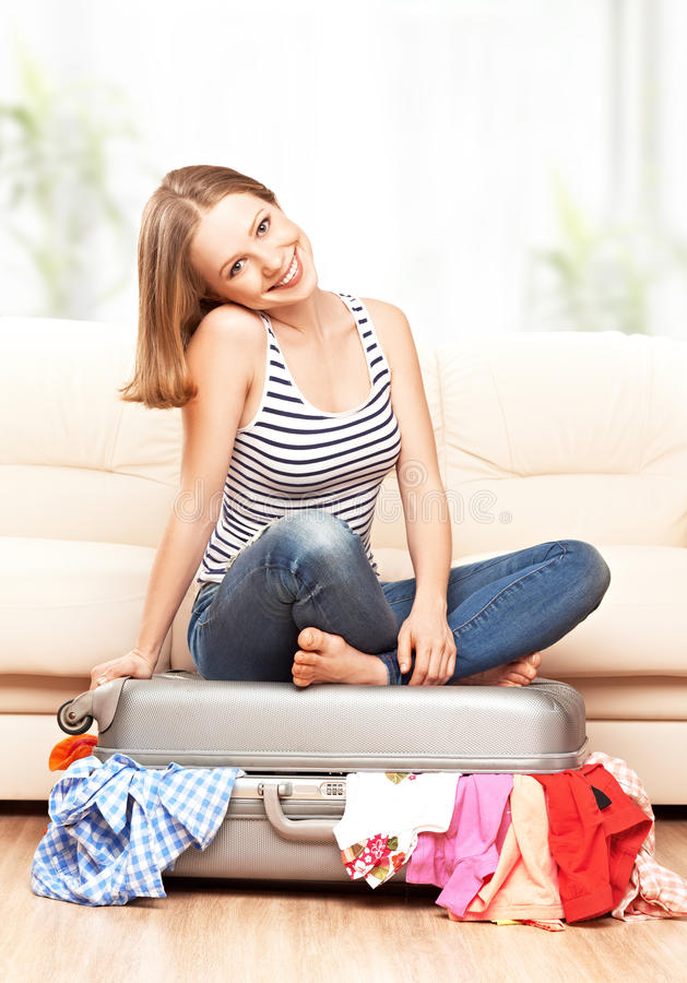 愉快的妇女在家包装手提箱 免版税库存图片
