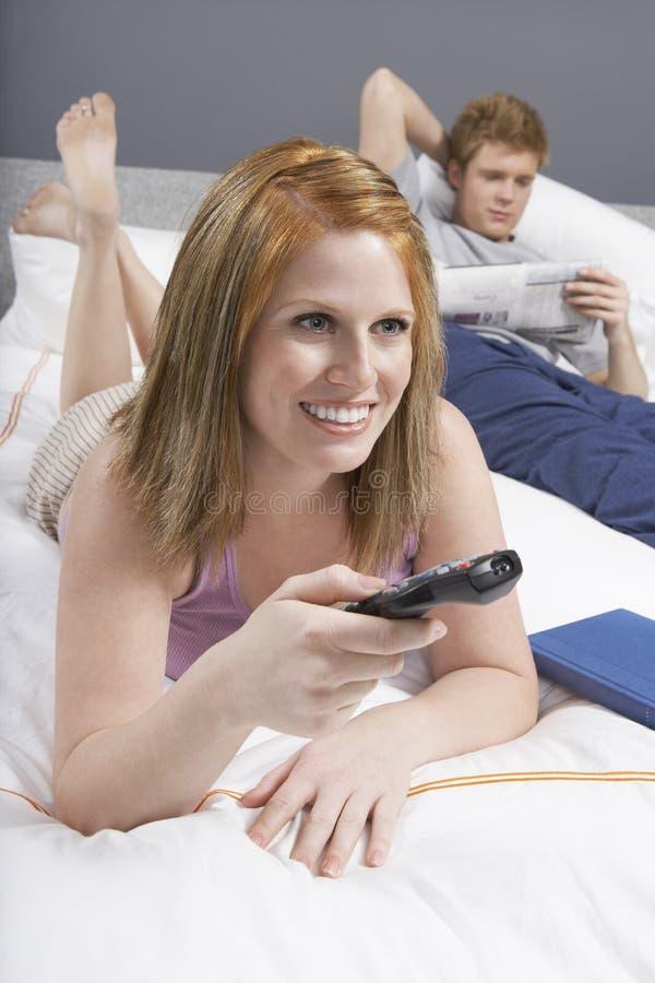 愉快的妇女在床上的看电视