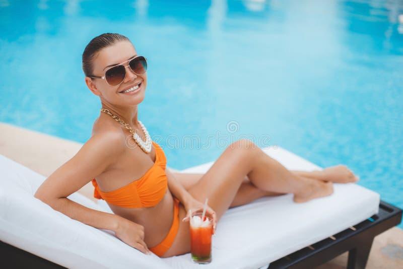 愉快的妇女在度假在蓝色水池附近的 免版税库存照片