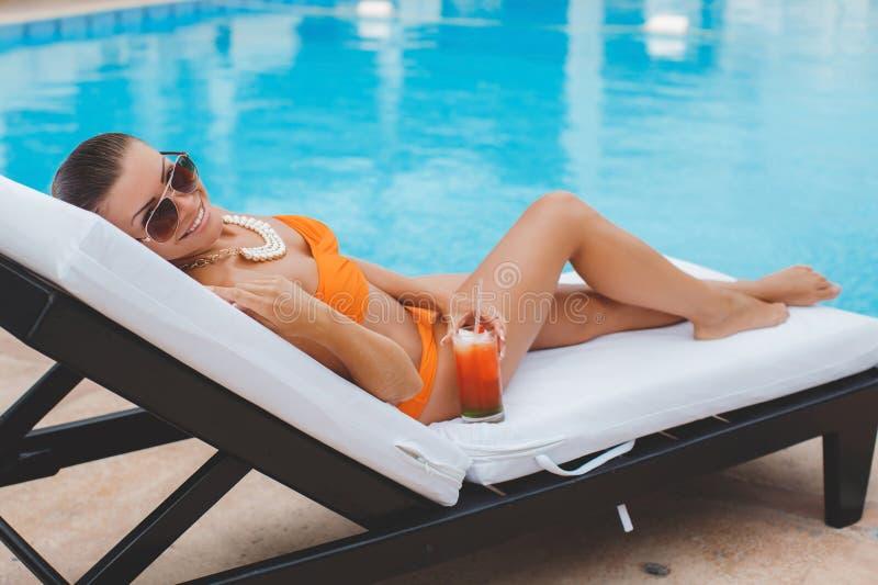 愉快的妇女在度假在蓝色水池附近的 免版税库存图片