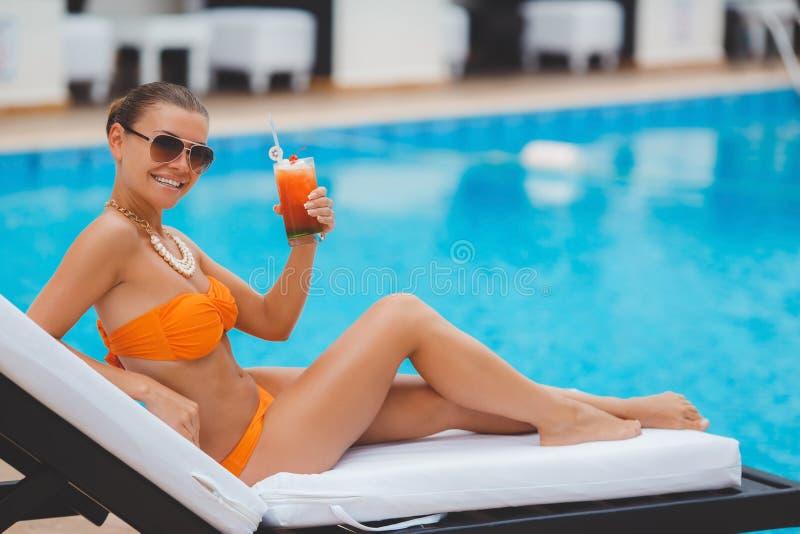 愉快的妇女在度假在蓝色水池附近的 库存照片