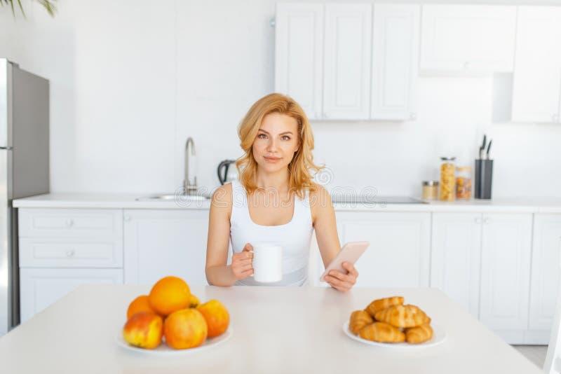 愉快的妇女在桌上用果子和烘烤 免版税库存图片