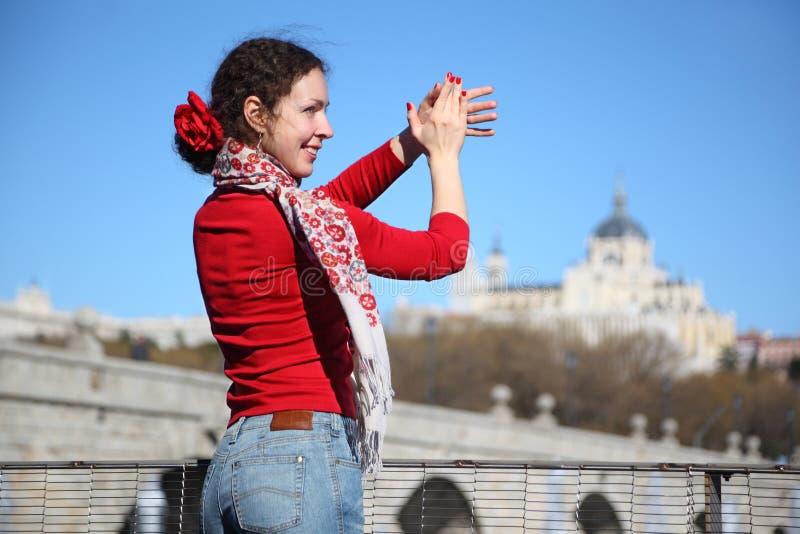 年轻愉快的妇女在桥梁附近显示佛拉明柯舞曲姿态 免版税图库摄影