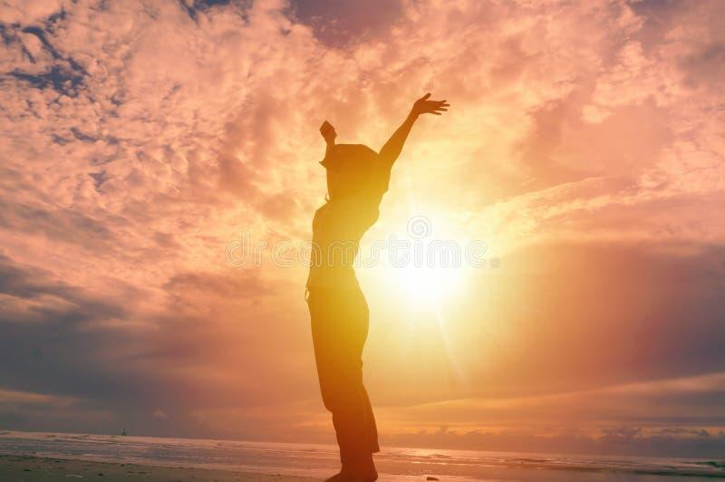 愉快的妇女在背景中的提高手和美好的日出 免版税库存照片
