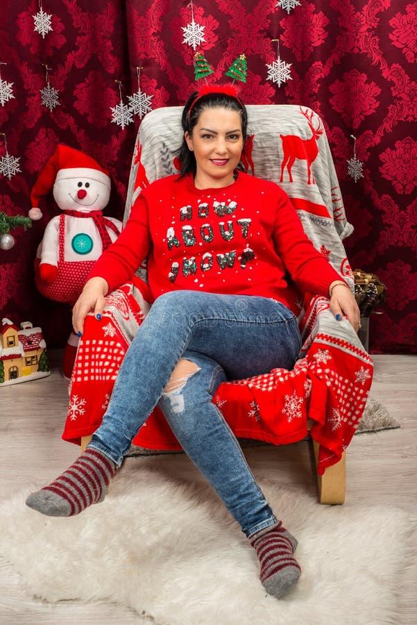 愉快的妇女坐与圣诞树的椅子 免版税库存图片