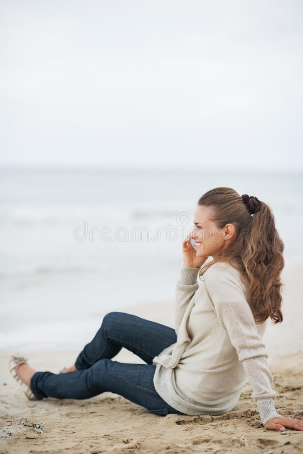 愉快的妇女坐偏僻的海滩和谈的手机 免版税库存照片