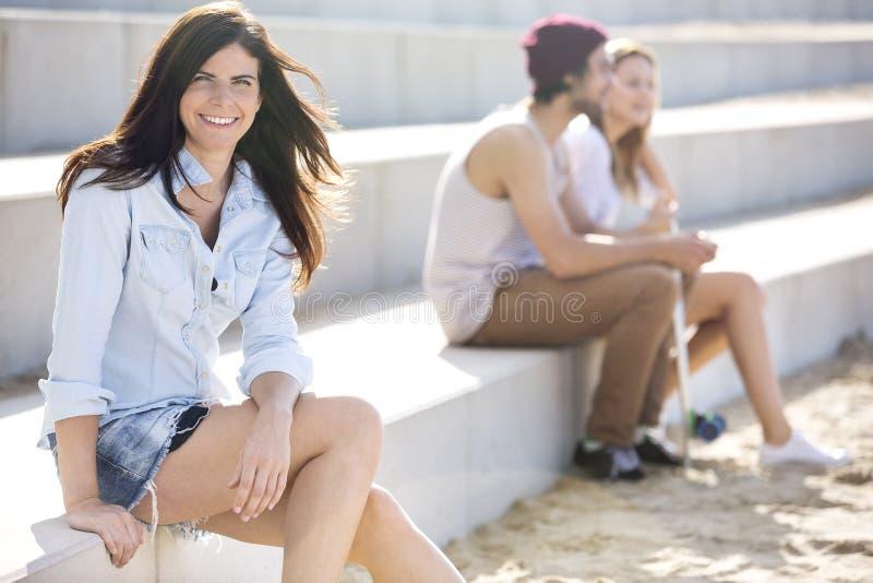 愉快的妇女坐步在海滩 免版税库存图片