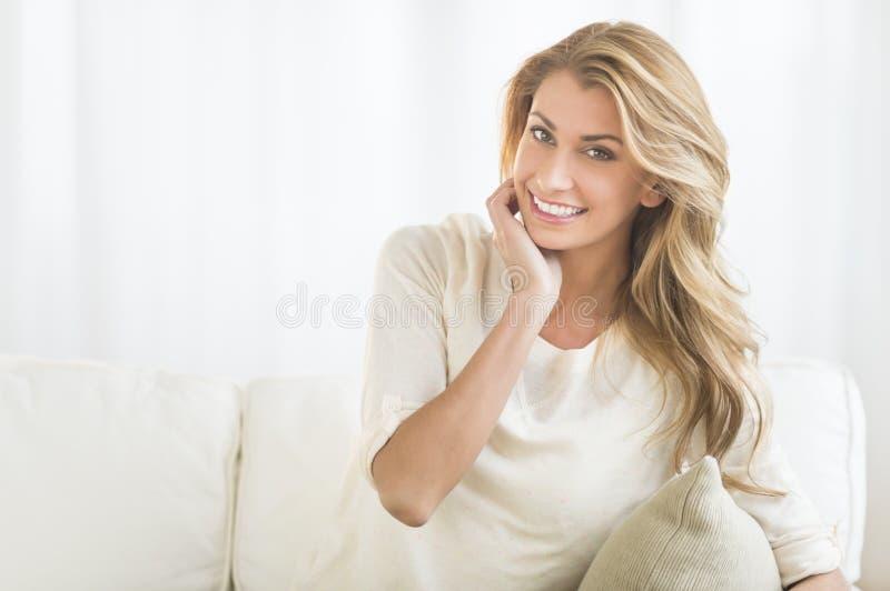 愉快的妇女坐沙发 免版税库存照片