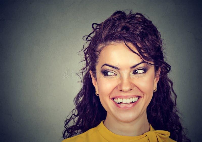 愉快的妇女微笑的看对边 免版税图库摄影