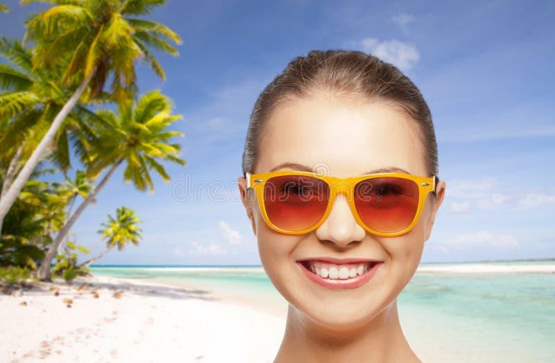 愉快的妇女或十几岁的女孩太阳镜的在海滩 免版税库存图片