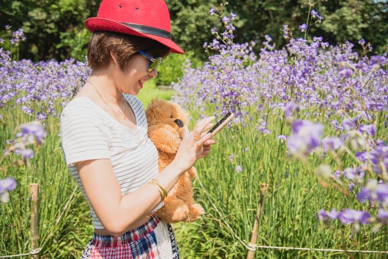 愉快的妇女拥抱玩具熊 绿色背景 库存照片