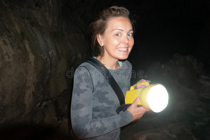 愉快的妇女探险家在加利福尼亚时拿着一个手电,当陷下和spelunking地下在火山岩床国家历史文物 免版税库存图片