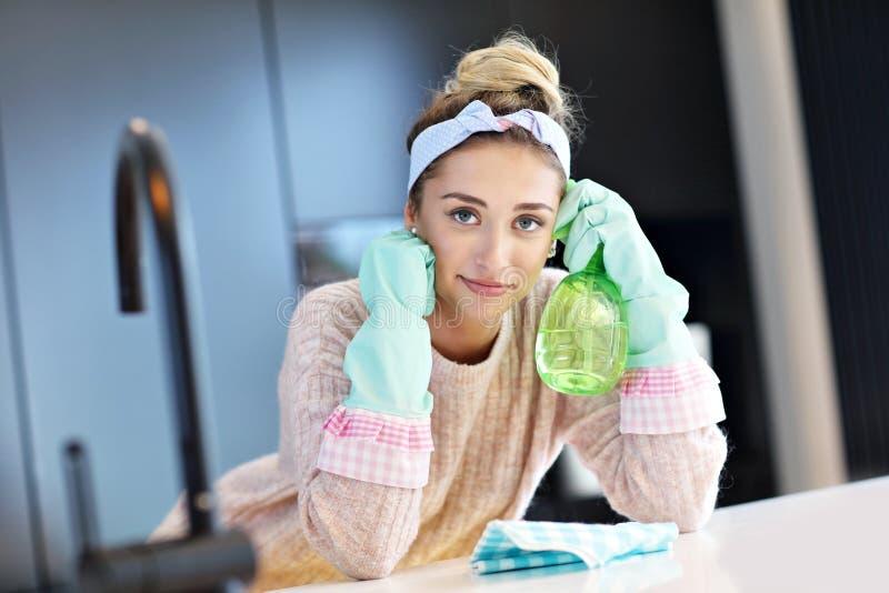 愉快的妇女清洁厨房工作台面 库存图片