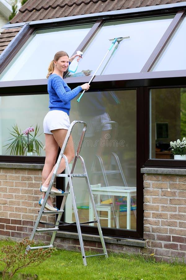 愉快的妇女清洁窗口户外 库存照片