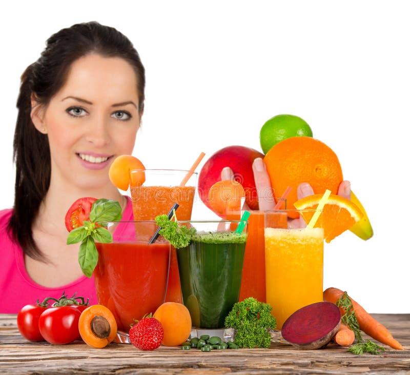 年轻愉快的妇女用新鲜水果汁 免版税库存图片