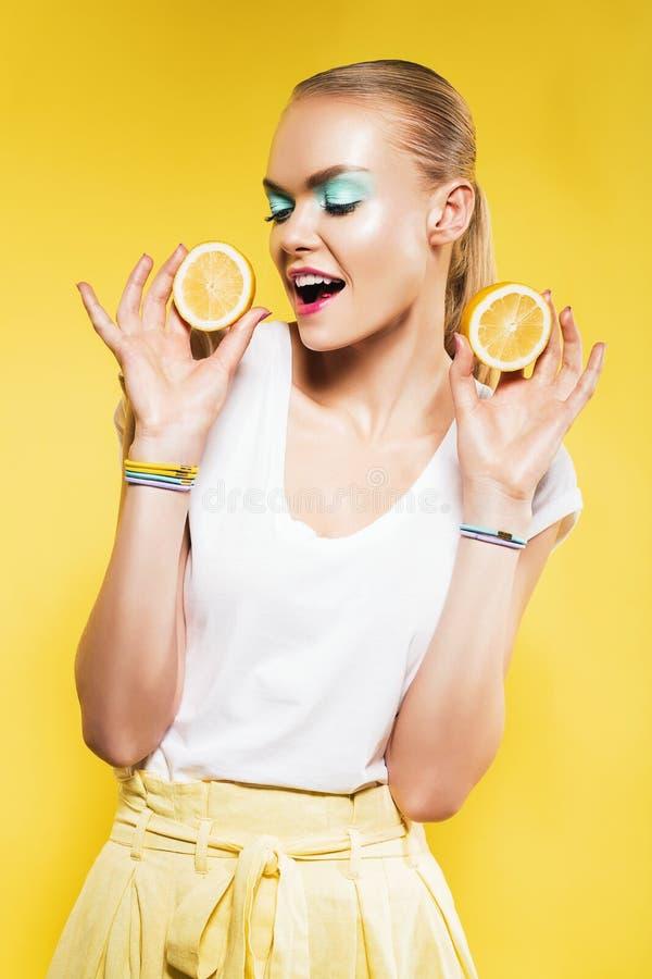 愉快的妇女用柠檬在手上 图库摄影