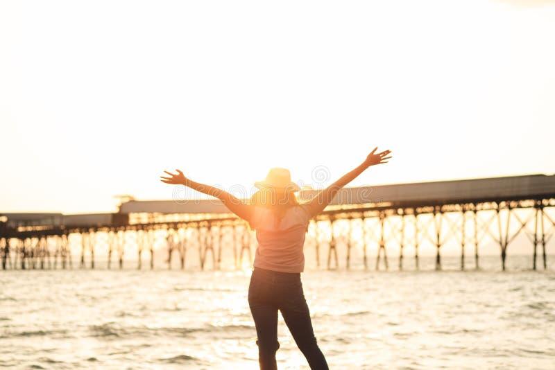 愉快的妇女用站起来在夏天机智的日落海滩的手 库存照片