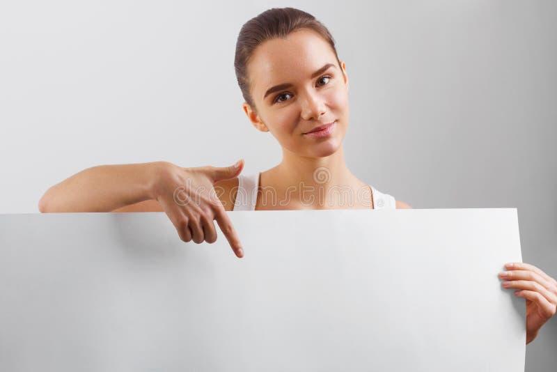 愉快的妇女画象,显示与copyspace的空的空白的牌 拿着一副大白色横幅的女商人 免版税库存图片